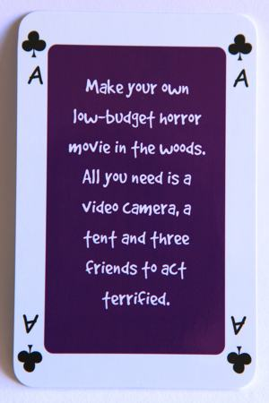Playing card Ace of clubs reads: Make your own low budget horror movie in the woods. All you need is a video camera, a tent and three friends to act terrified.