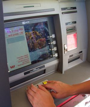 A photo of a person covering the number pad while entering their PIN into an automatic teller machine