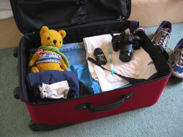 Photo of a suitcase being packed for holiday. It contains clothes, camera gear and a soft toy.
