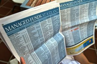 Photo of an open newspaper with multiple columns containing lists of the names of managed funds