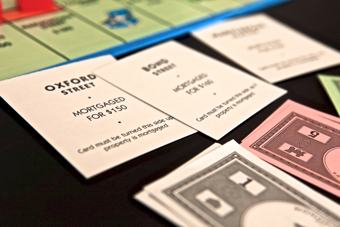 Photo of a monopoly game in progress. One player is not going very well and has had to turn many of his property cards over, indicating that he has mortgaged these back to the bank.