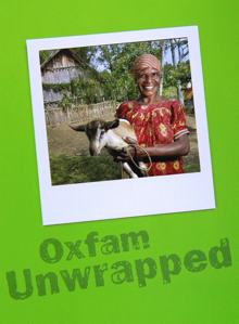 Photo of an African woman in a village. There is a thatched roof house in the background and she is wearing simple clothing, no makeup and no jewelry. She is holding a small goat and looks very happy to have the animal in her arms.