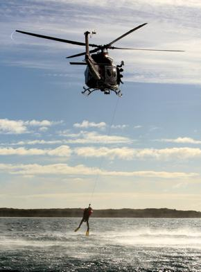 A photo of a rescue helicopter pulling a person from the water