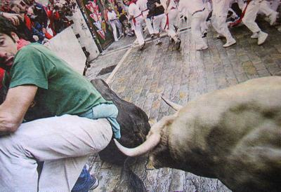 Photo of a tourist in Spain attending the annual running of the bulls. In the background are many people running and looking behind them. In the foreground the man's left knee is bent right up next to his elbow. He is looking in horror behind him at the tip of the horn of a muscular bull which is currently millimeters away from ripping him a second arsehole.