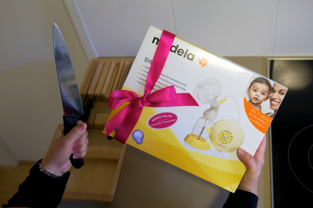 Photo of a breast pump still in the box with a red ribbon wrapped around it. It is being held in the recipient's right hand while their left hand holds a large kitchen knife.