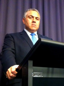 Photo of federal Treasurer Joe Hockey standing at a lectern during a press conference, looking straight at the camera, not looking happy. He never looks happy.
