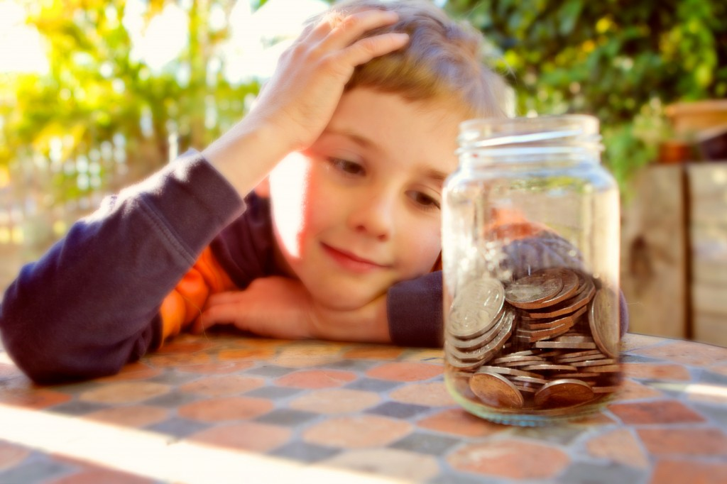 Photo of a piggy bank with a young boy in the background.