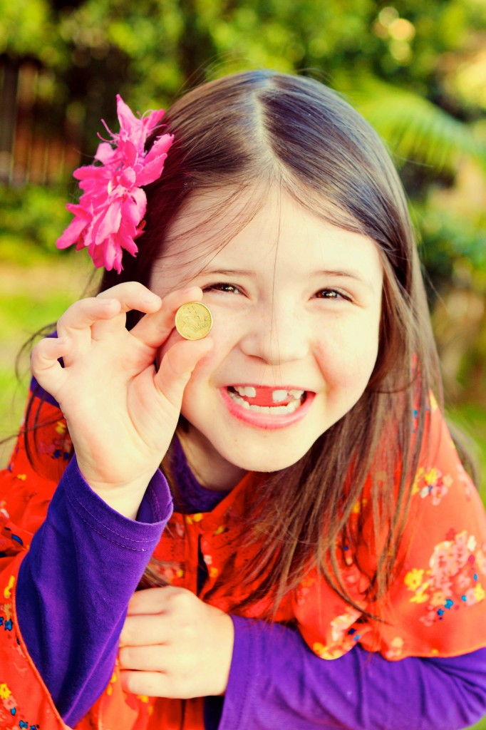 Close up photo of a smiling young girl holding a 2 dollar coin up next to the space where her tooth used to be.