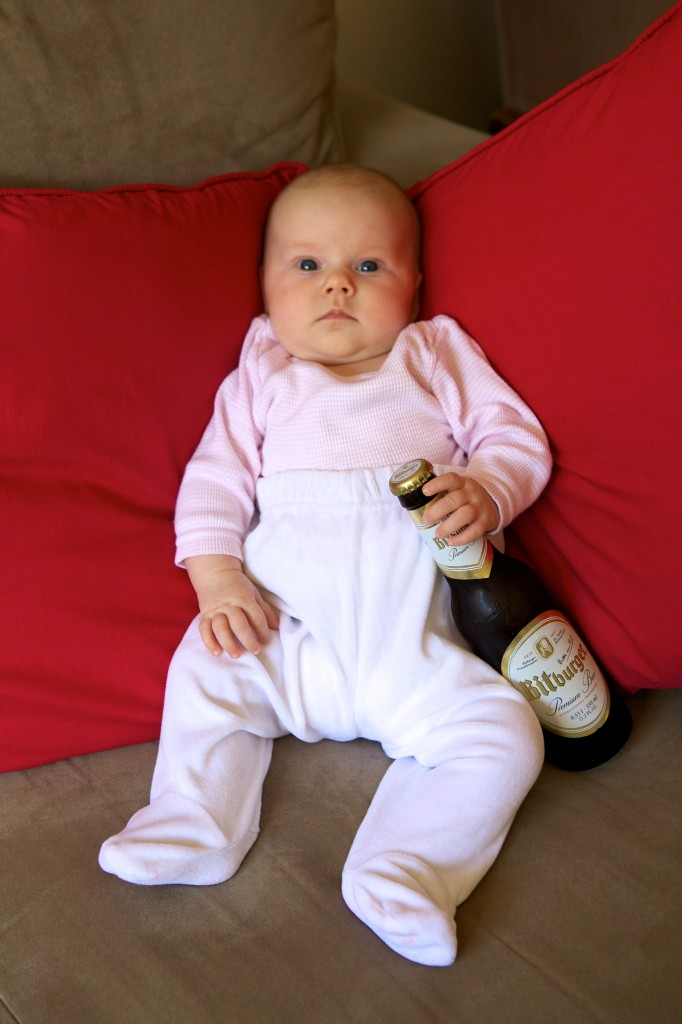 Photo of our 2 month old daughter sitting on the lounge with an unopened bottle of German beer propped between her legs.