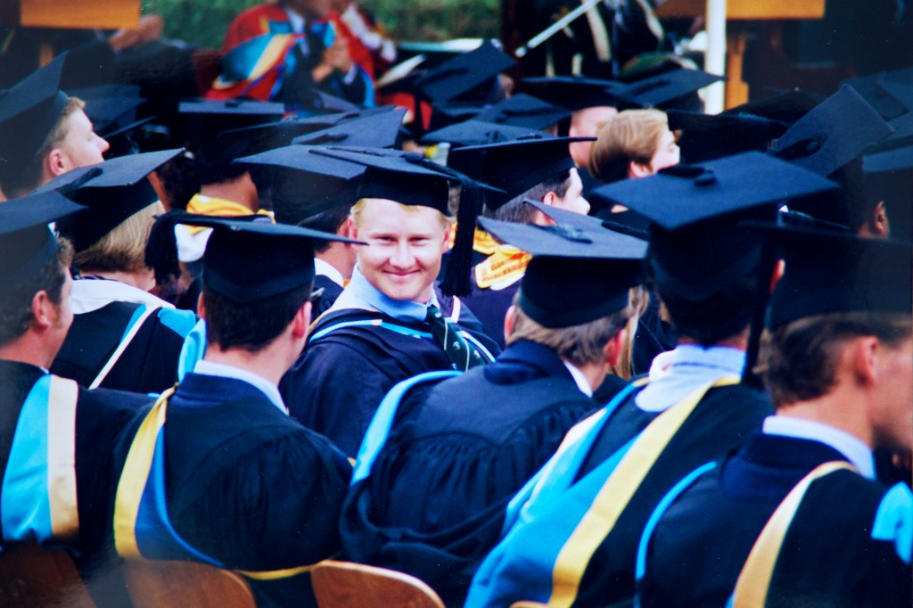 Photo of a graduate wearing cap and gown in a crowd of others. All the graduates are looking away from the camera except for the guy in the middle who is looking straight at the camera and is obviously pretty happy with himself.