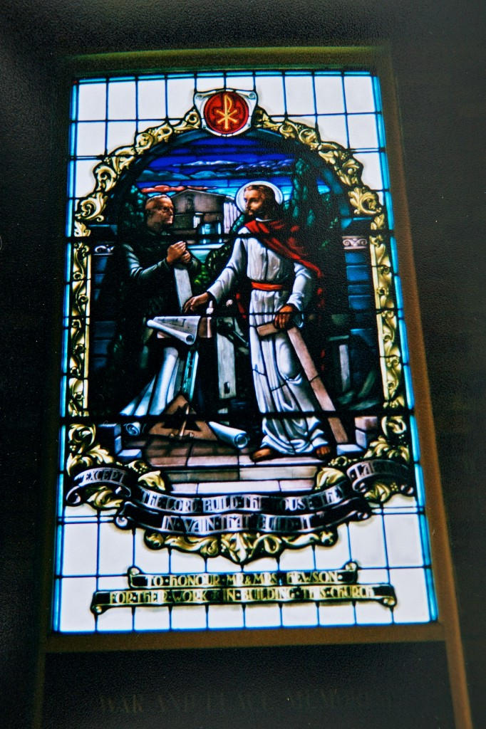 Photo of a stained glass window showing two men, one kneeling, one standing, and a table between them with what looks like building plans.