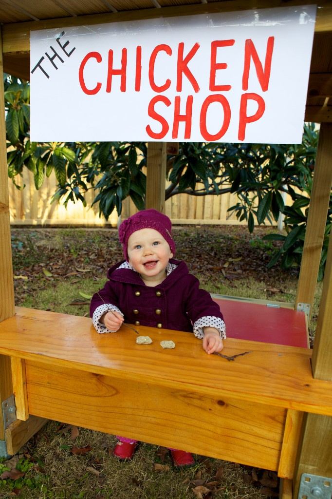 "Photo showing our daughter on her play equipment in our backyard. She is standing behind a very small counter, above which is a sign that reads ""The chicken shop"". On the counter are two small rocks and a stick. She is looking towards the camera with a big smile."