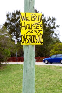 "Photo of a sign that reads ""We buy houses fast"" with a mobile number below."