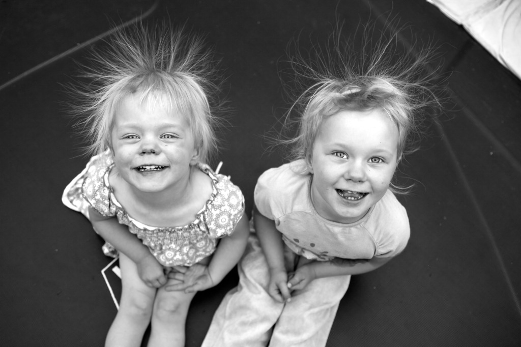 B&W photo of two girls sitting on a trampoline with hair going in all directions due to static electricity.