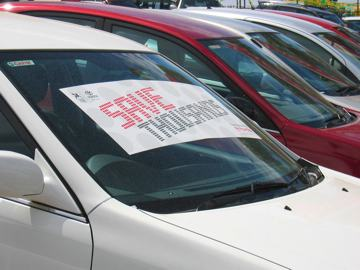 A photo of a car for sale with a sign over the windscreen that reads save thousands