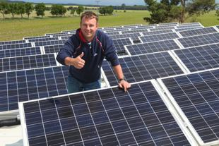 Photo of my brother-in-law standing on a rooftop surrounded by solar panels. He is smiling with pride.