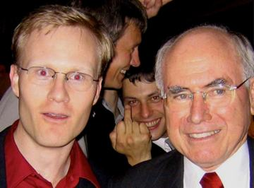 This photo was taken a few years ago. I am on the left and former Prime Minister John Howard is on the right. In the background in between us is the cheeky colleague. He has a big grin, is looking straight to the camera and is sticking his middle finger up