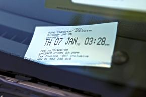 A photo of a parking ticket on the wind screen of a car