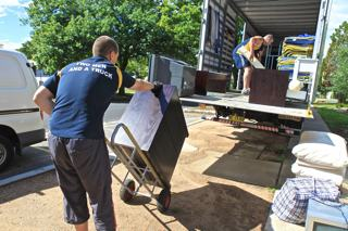 A photo of a removalist moving a item of furniture on to a removal truck