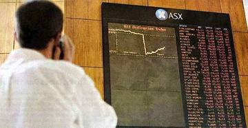 Photo of the back of a man's head as he looks up at a large monitor showing a graph in the Australian Stock Exchange building. The graph is showing the day's price on a share. Up until about midday the line is fairly flat. Then suddenly it drops down like a cliff in an almost completely vertical fall before regaining a bit of the loss by late in the day. He is holding a mobile phone to his ear.