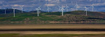 A photo of many wind turbines over looking a lake