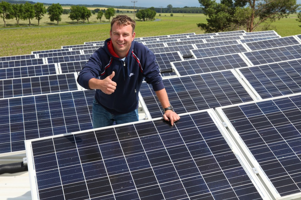 Photo of a man surrounded by pv solar giving the camera the thumbs up.