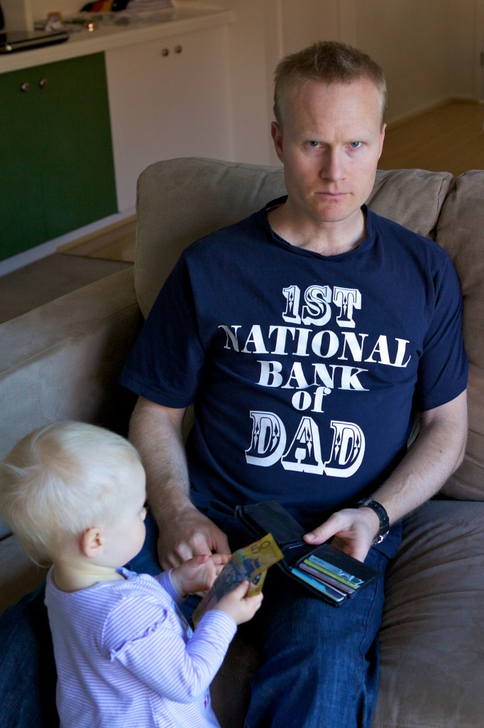 Photo of myself holding an open wallet handing our daughter a fifty dollar note. I have a look of annoyance on my face and am wearing a shirt that reads: First National Bank of Dad.