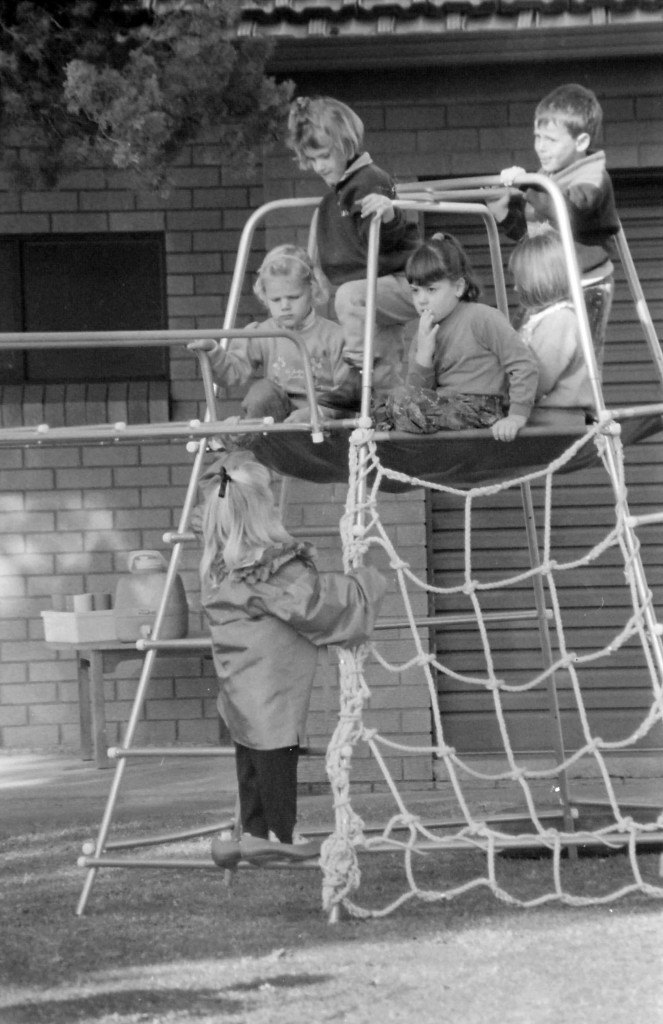 A black and white photo of a bunch of children playing on equipment in the grounds of a pre-school.